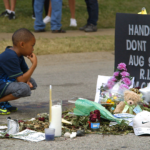 A young boy is seen observing the Michael Brown memorial site in Ferguson, Missouri. Courtesy of VANISH Films.
