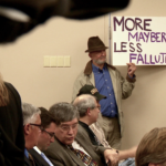 A protestor holds a sign at a Concord, New Hampshire city council meeting. Courtesy of VANISH Films.