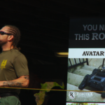 A SWAT team member stands next to an advertisement for robots at the 2014 SWAT Team Competition in Orlando, Florida. Courtesy of VANISH Films.