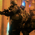 Cops in Ferguson, Missouri prepare to raid a storefront. Courtesy of VANISH Films.