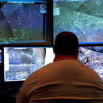 An analyst inspects video feeds of a wide-scale aerial surveillance system being utilized by local police departments. Courtesy of VANISH Films.